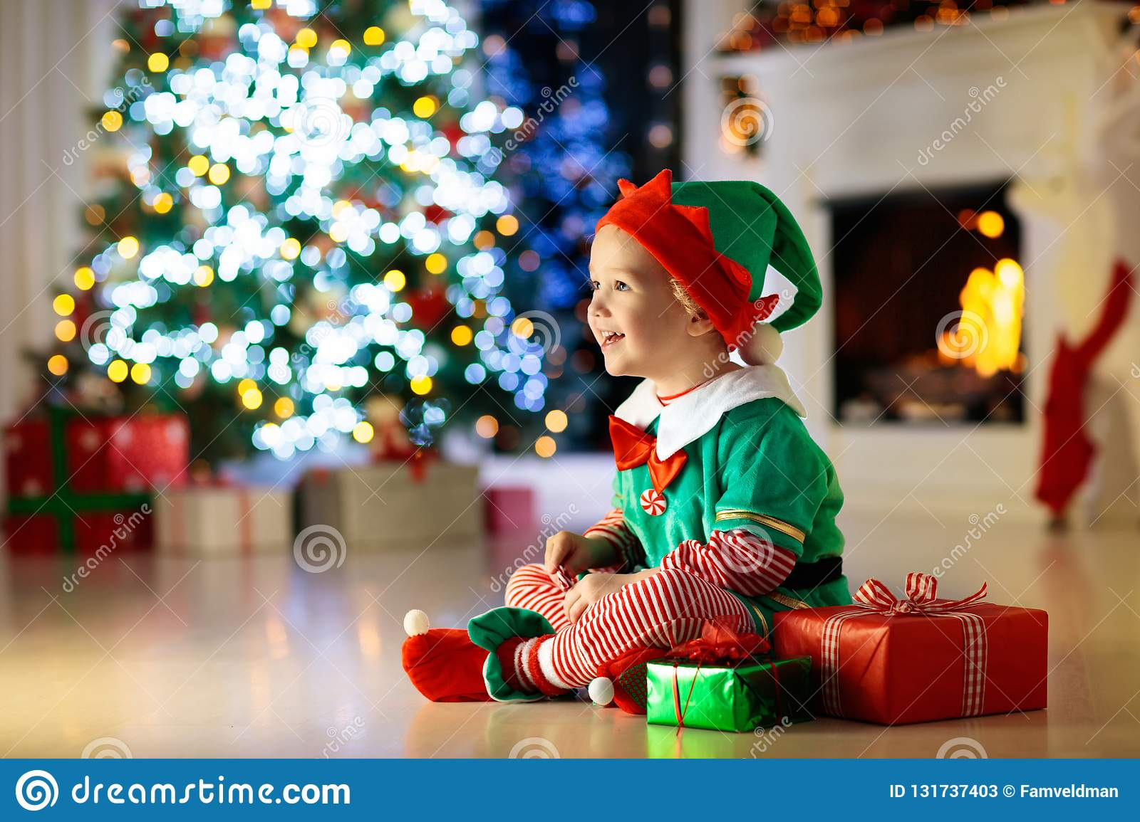 Child opening present at Christmas tree at home. Kid in elf costume with Xmas gifts and toys. Little baby boy with gift box and