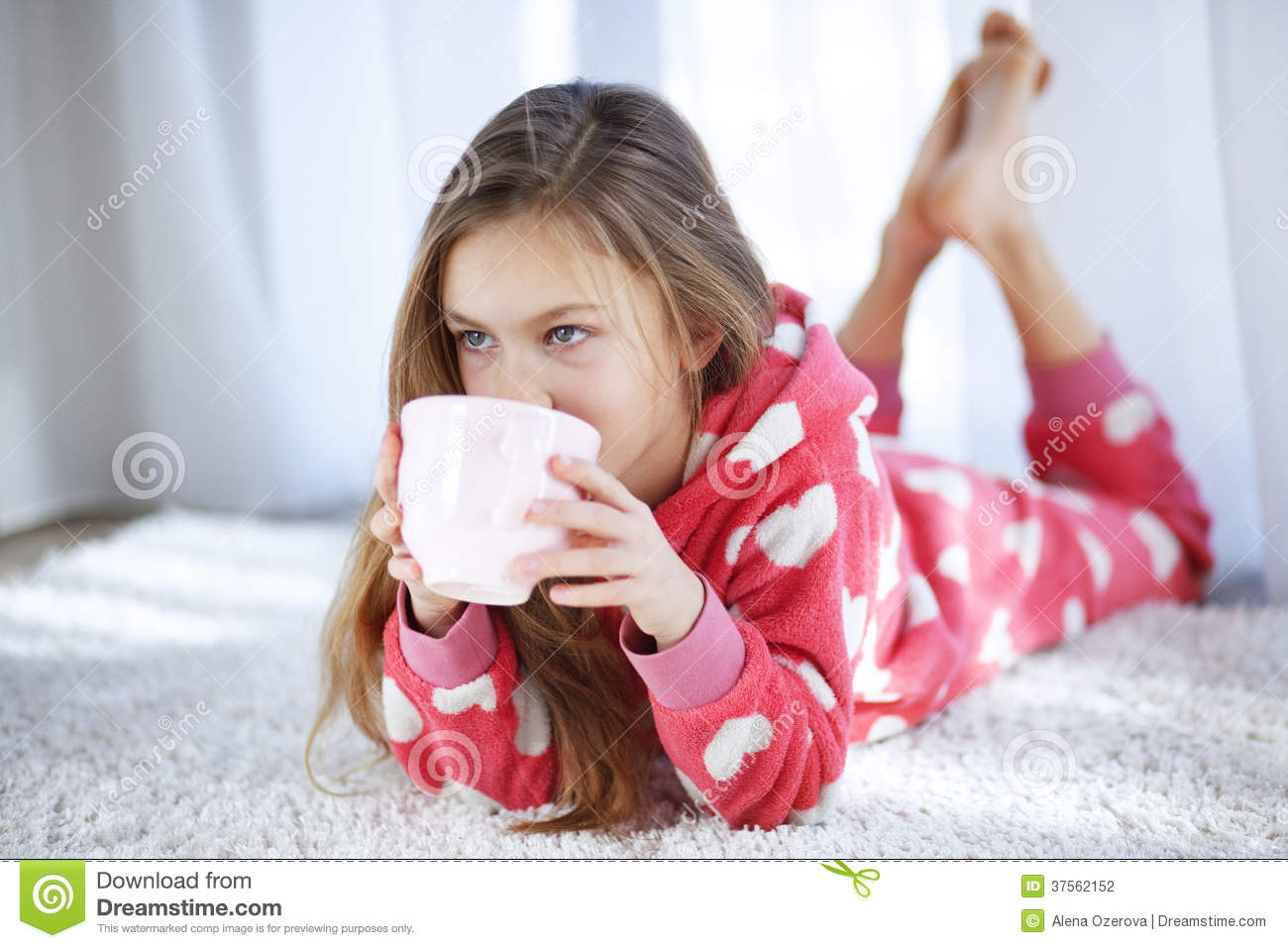 Portrait of child in soft warm pajamas lying down on the carpet at ...