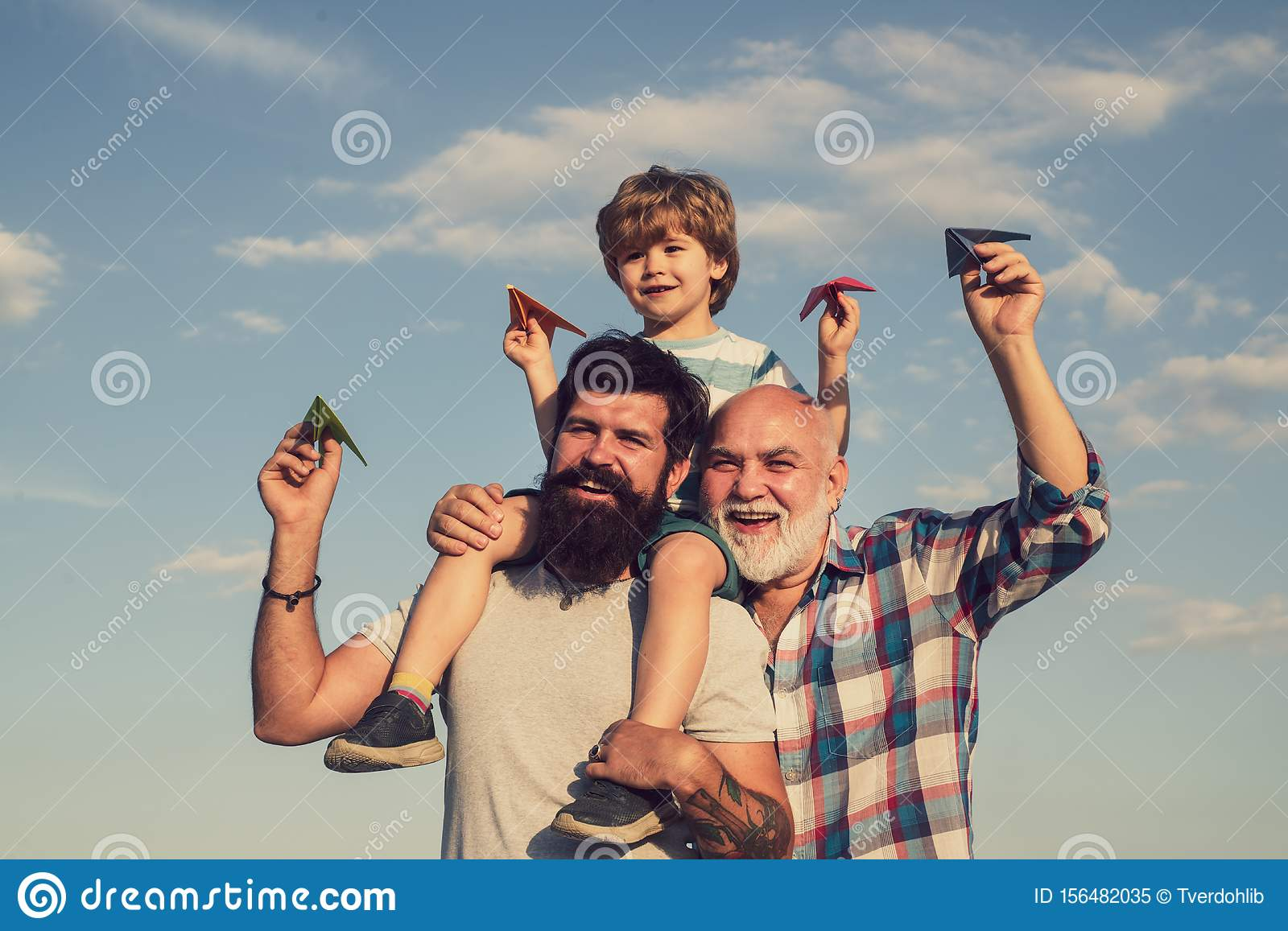 Child pilot aviator with paper airplane dreams of traveling. Dream of flying. Cute son with dad playing outdoor. Father