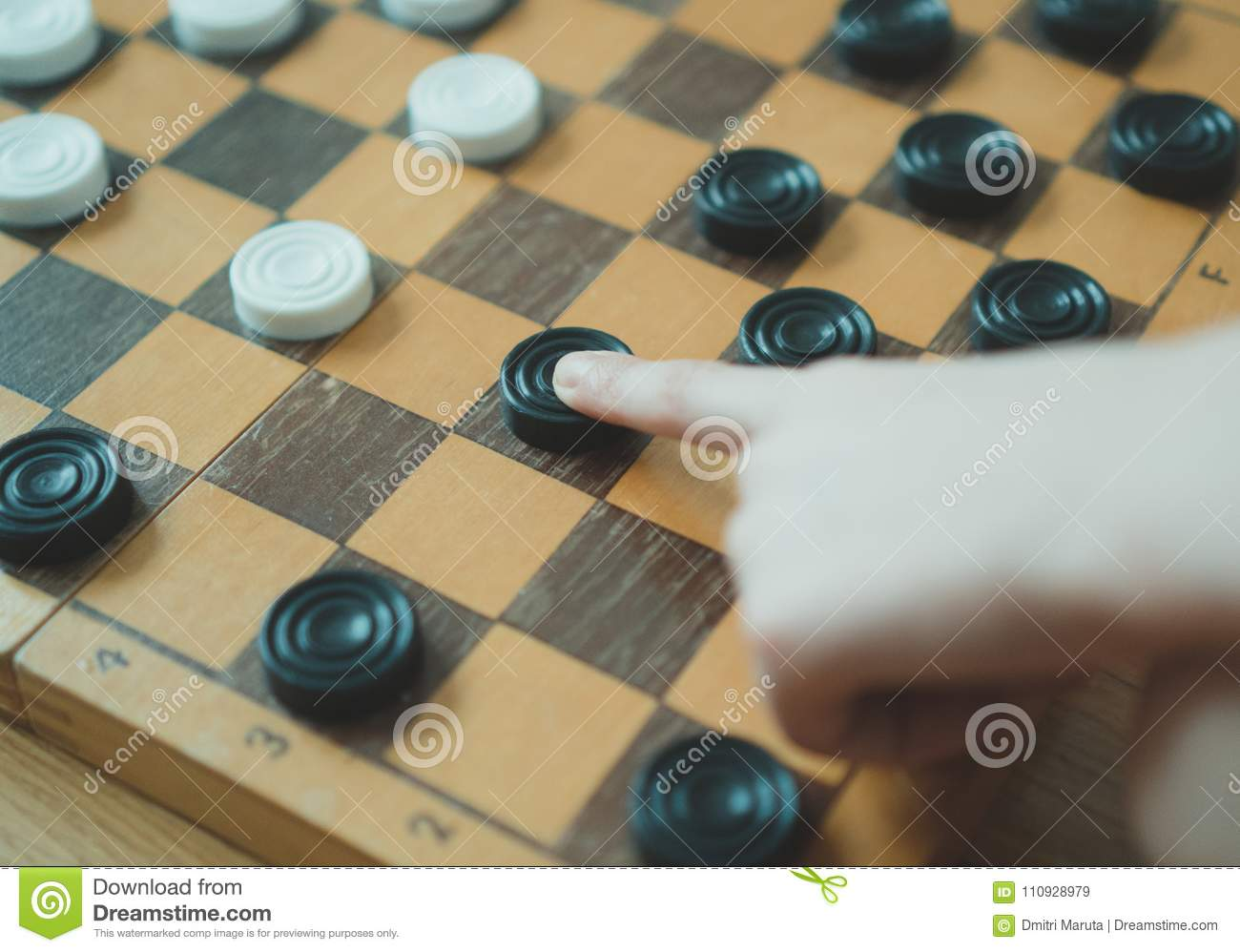 Child playing checkers board game.