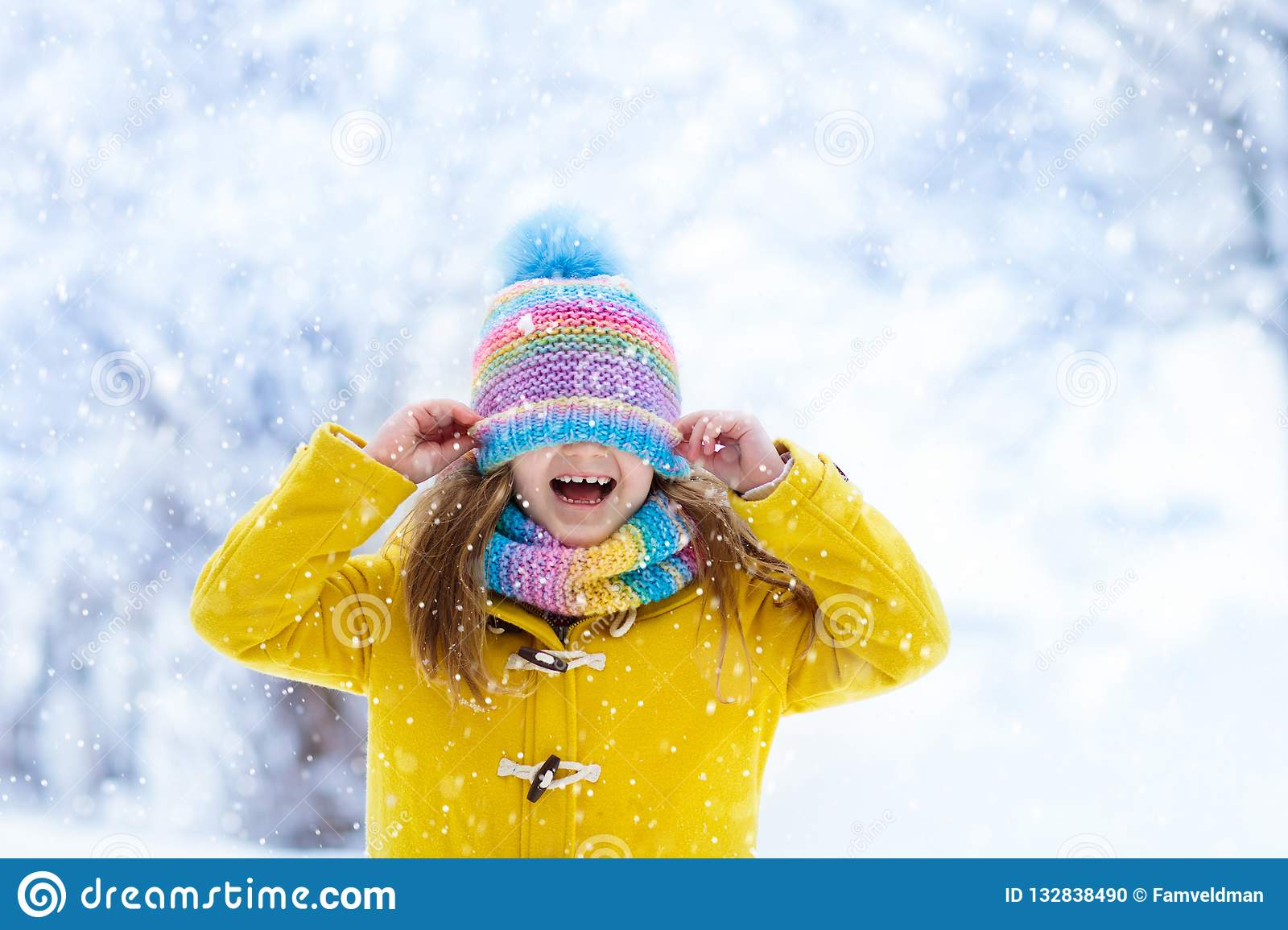 Child playing in snow on Christmas. Kids in winter