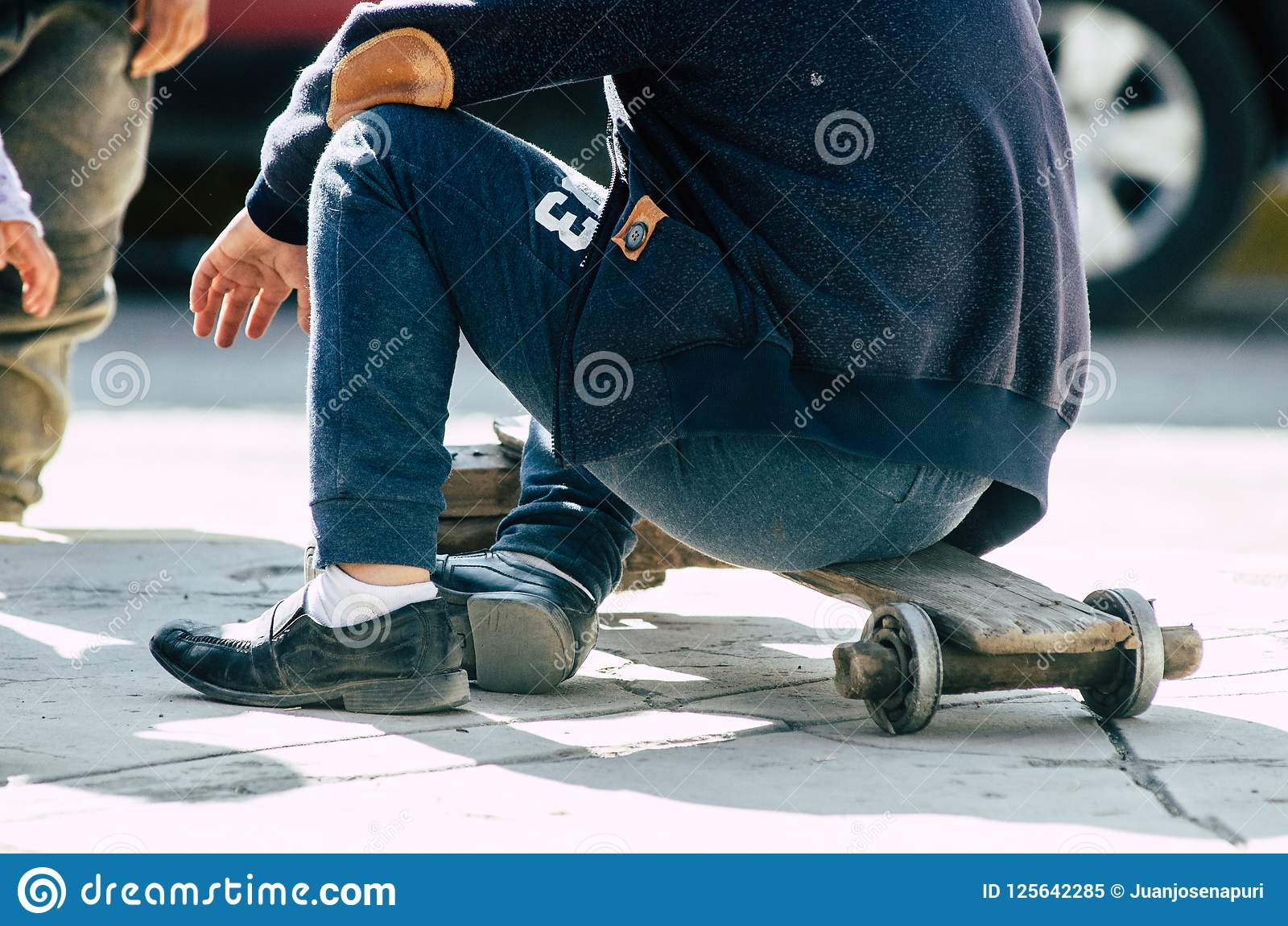 Child playing on the street with a handmade skateboard