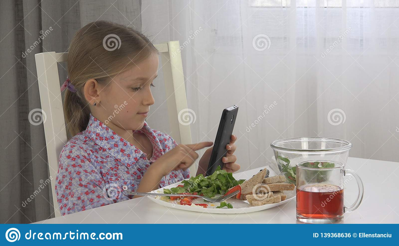 Child Playing Tablet, Kid Use Smartphone Eating Eggs, Salad Lettuce at Breakfast