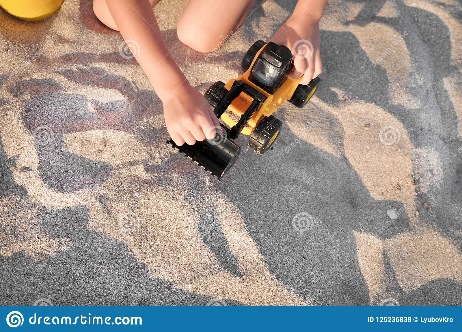 Child playing with a toy tractor on the beach.