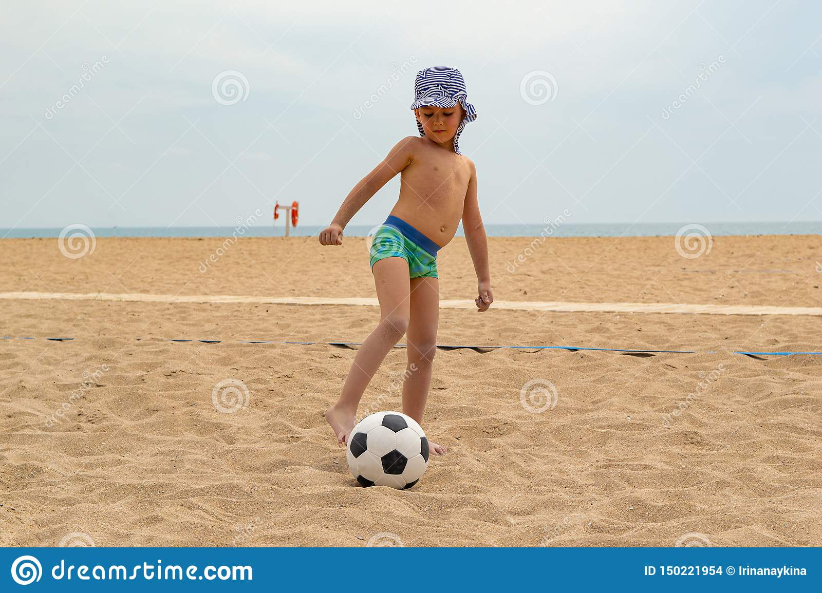 The child plays football on the beach