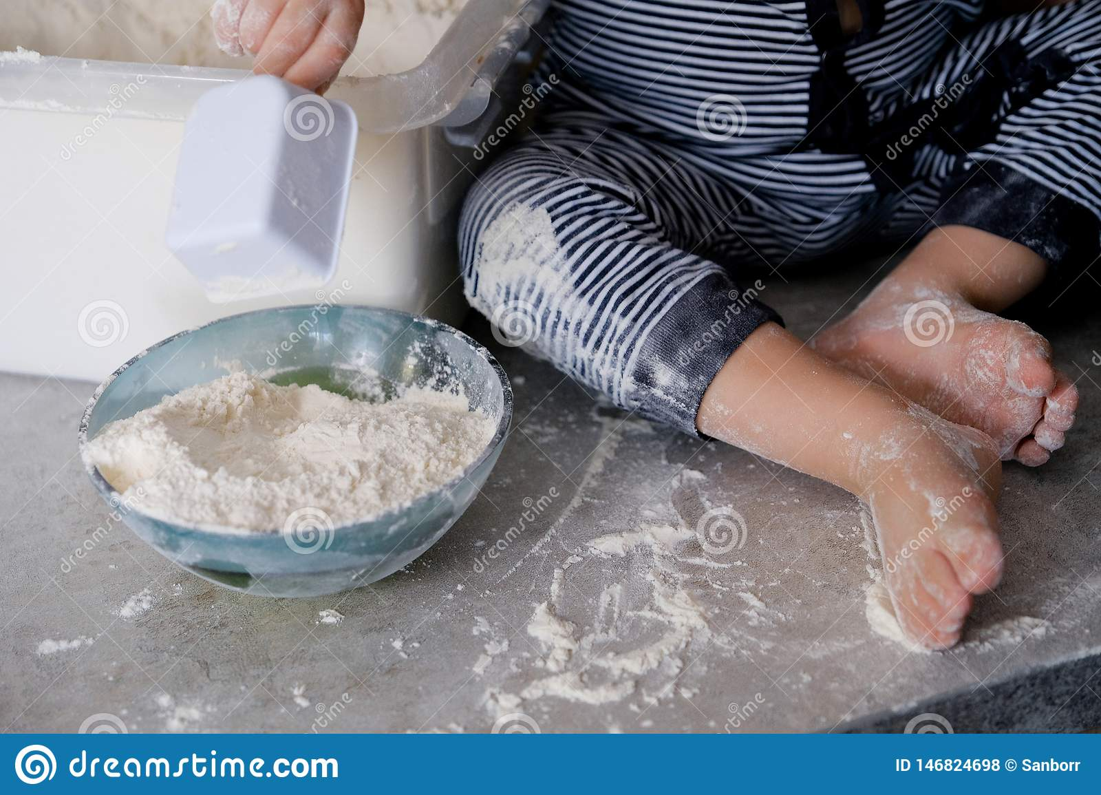 The child plays and indulges in flour on the kitchen table. Children`s feet are stained with white flour . Feet of the little coo