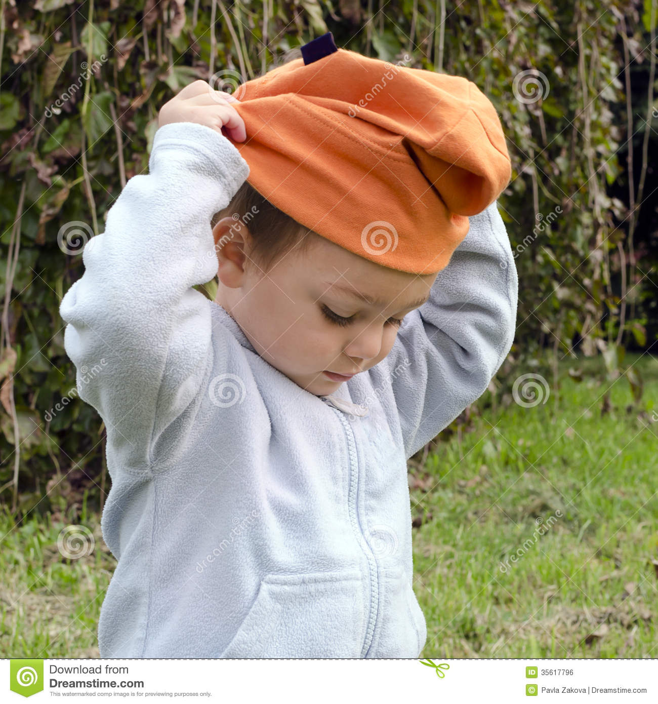 Child Putting On Hat Royalty Free Stock Image - Image: 35617796