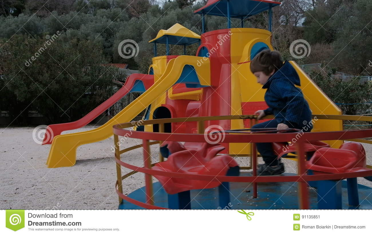1d2dc97d7 The Child Quickly Spin On The Carousel In The Playground In The Spring Stock  Video - Video of leisure, play: 91135851