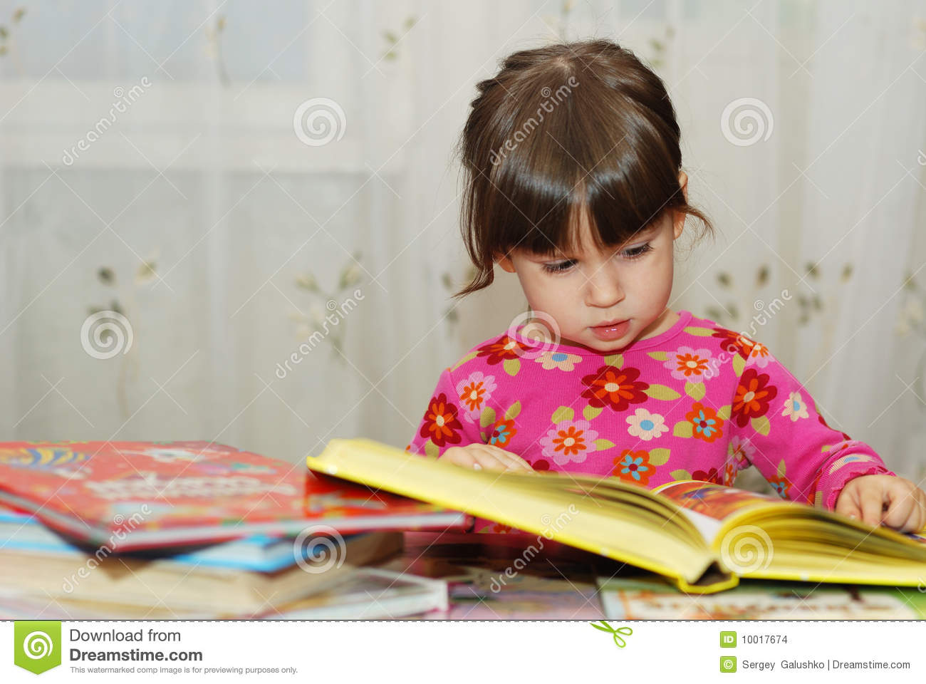The child reading the book. The three-year girl in house conditions.