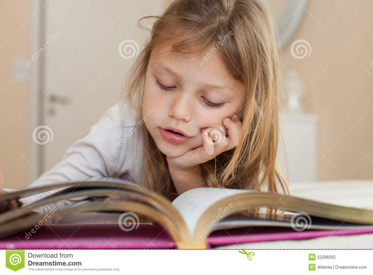 Portrait of a little girl reading a book
