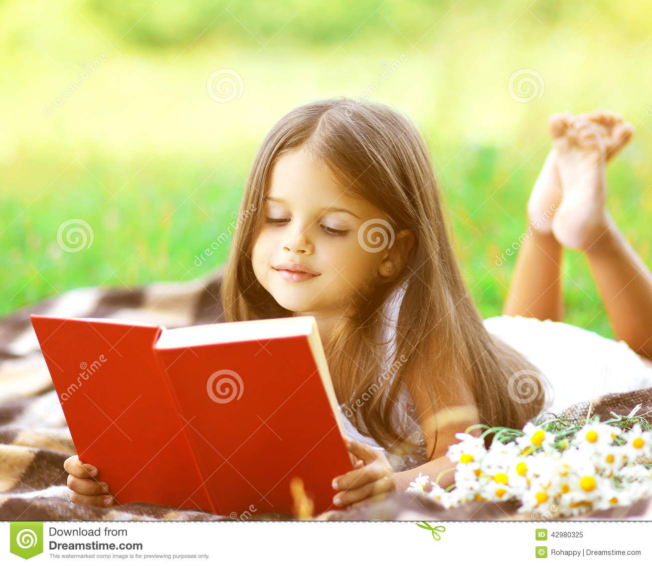 child reading a book on the grass stock image image of healthy