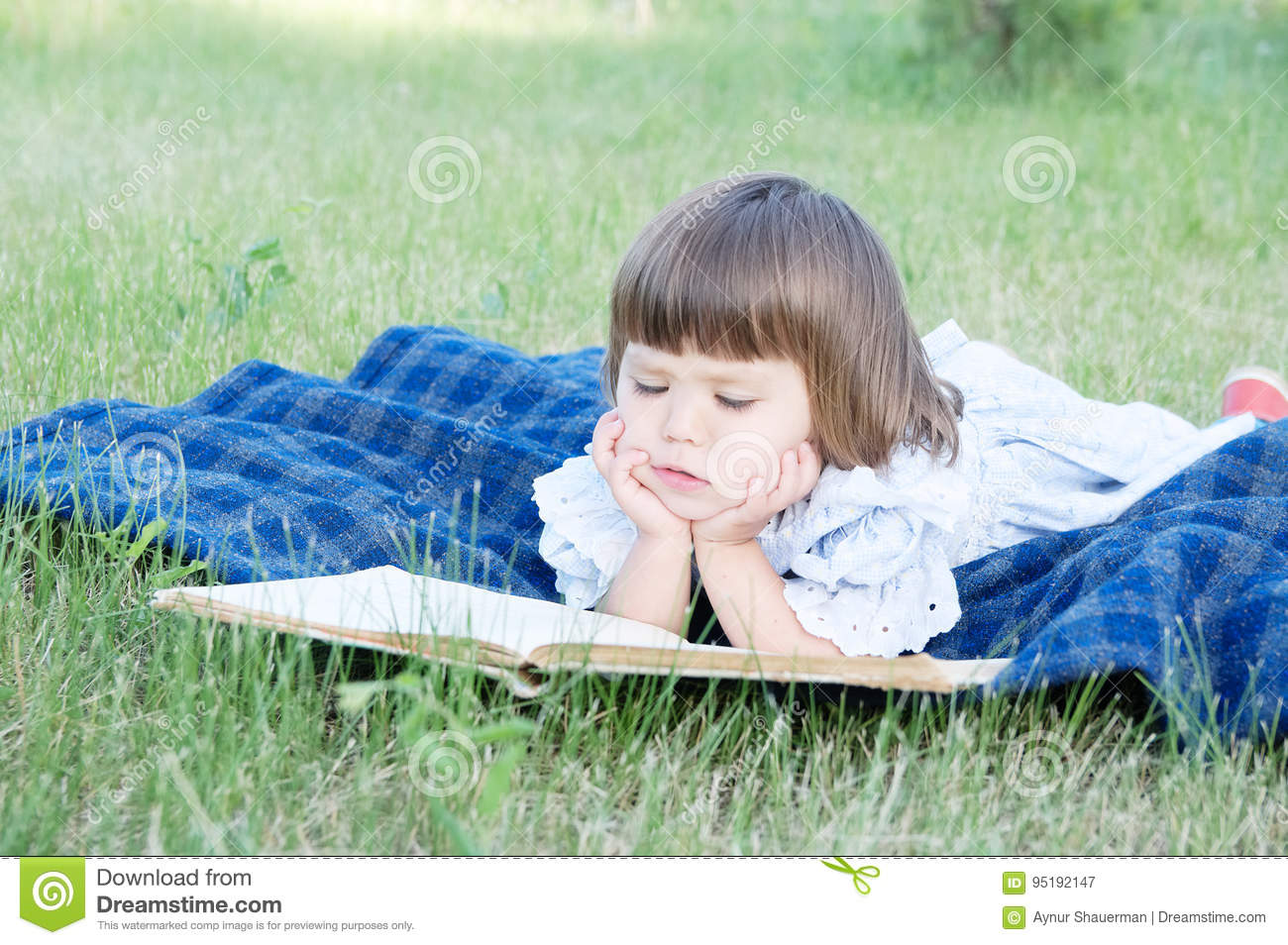 child reading book lying on stomach outdoor, smiling cute little
