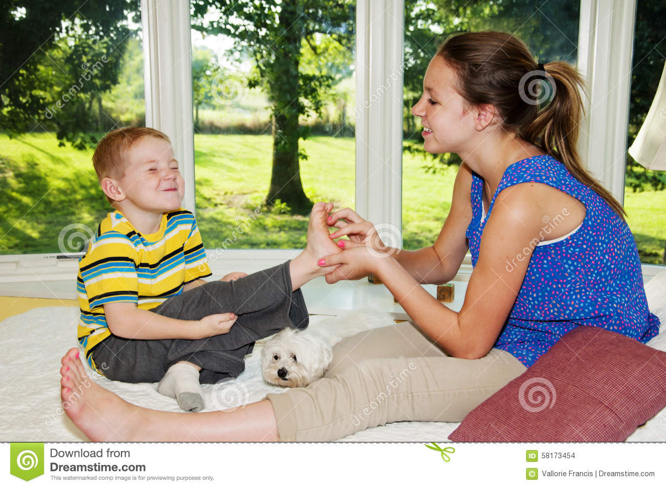 Child ready to laugh while foot tickled by girl