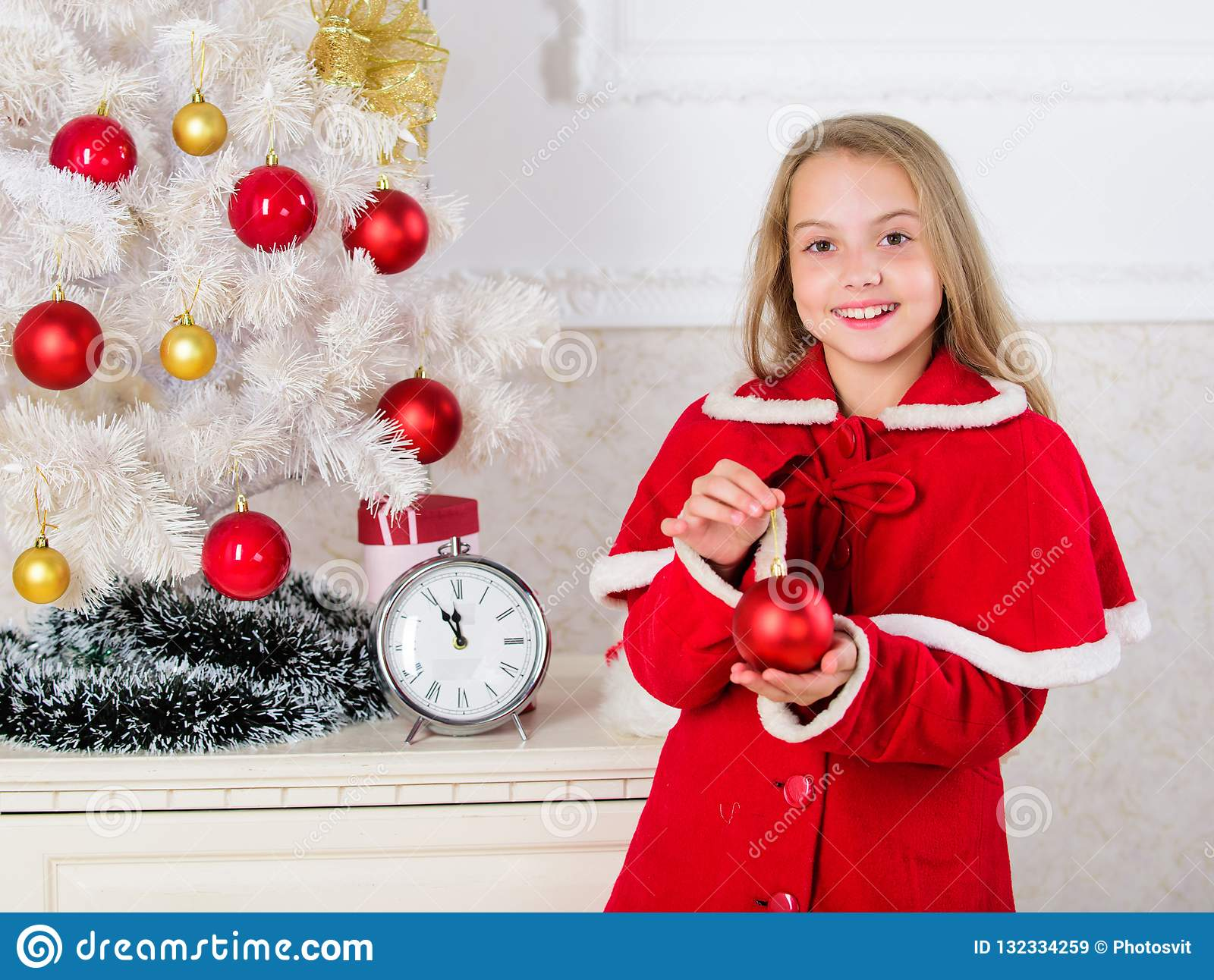 Child red costume hold christmas ornament ball. Christmas ball traditional decor. Kids can brighten up christmas tree by