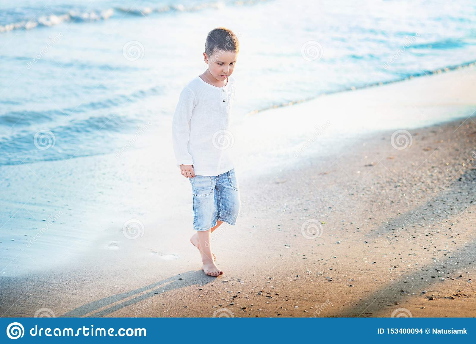 Child running on the beach. Summer vacation. happy kid playing on beach at the sunset time