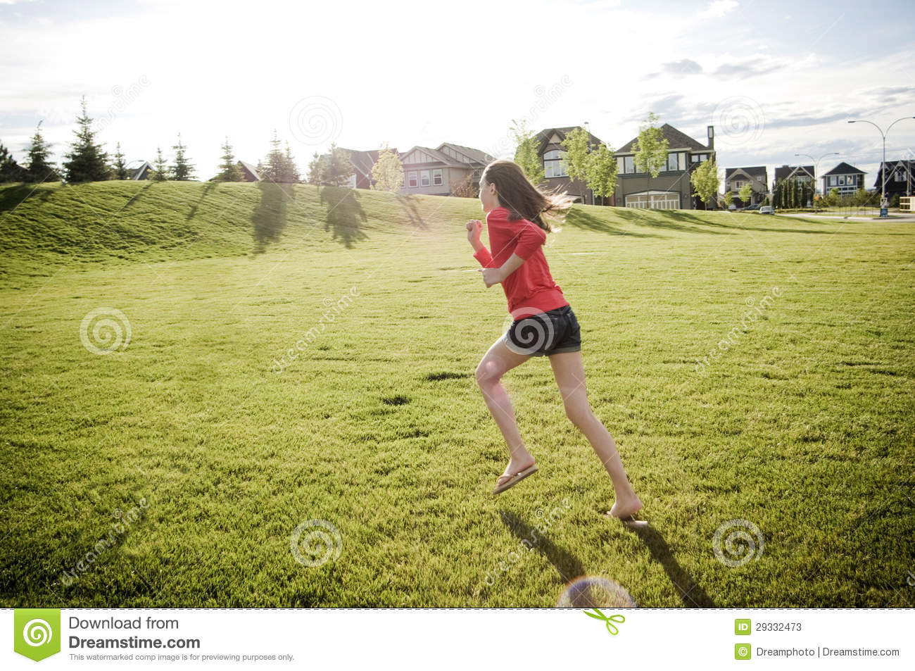 Teen girl running in the open field in her community in summer with