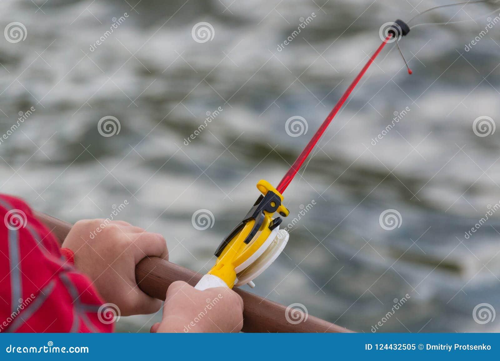 A child`s hand is fishing on a small fishing rod. Ozernaya fishing.
