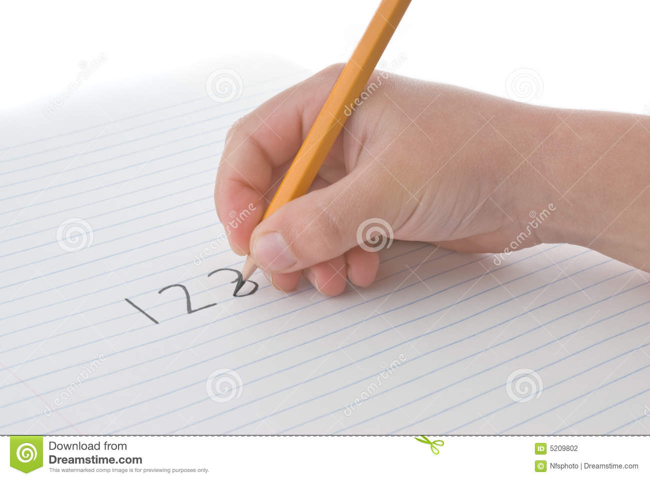 child's hand holding pencil, writing numbers on paper stock photo