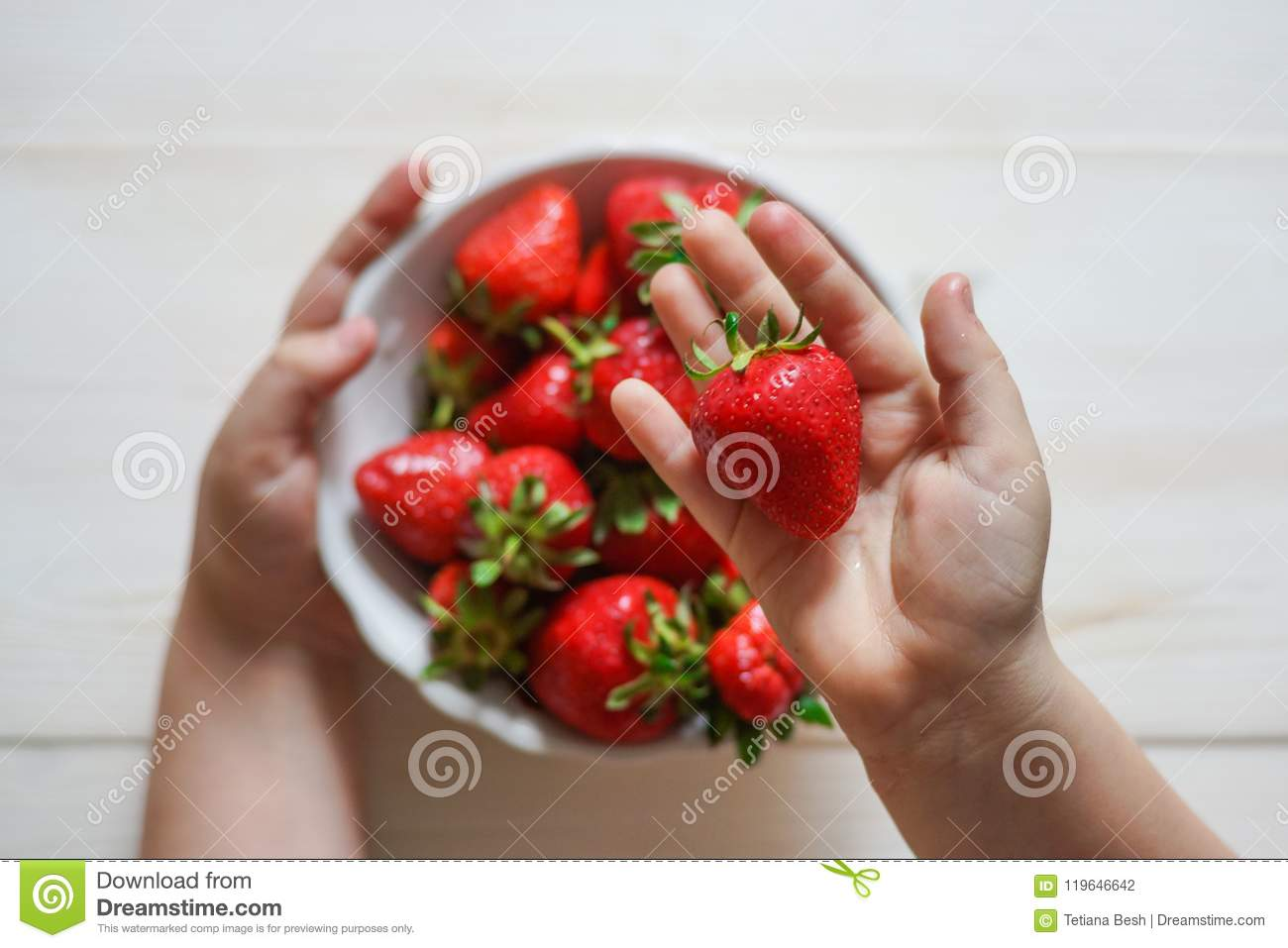 Child& x27;s hand holding strawberry on rustic concrete background. Summer healthy eating concept. Top view