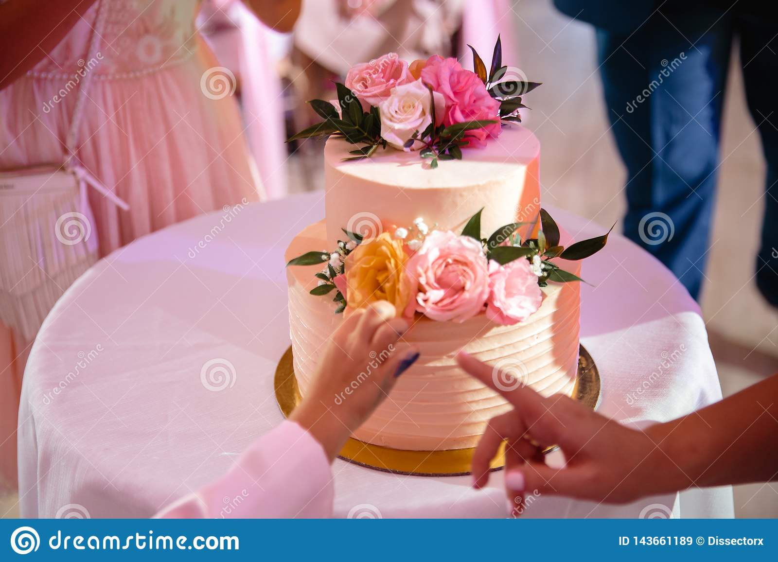 A child`s hand leaning toward the wedding cake in ecological natural style - His parent shows with her finger that he