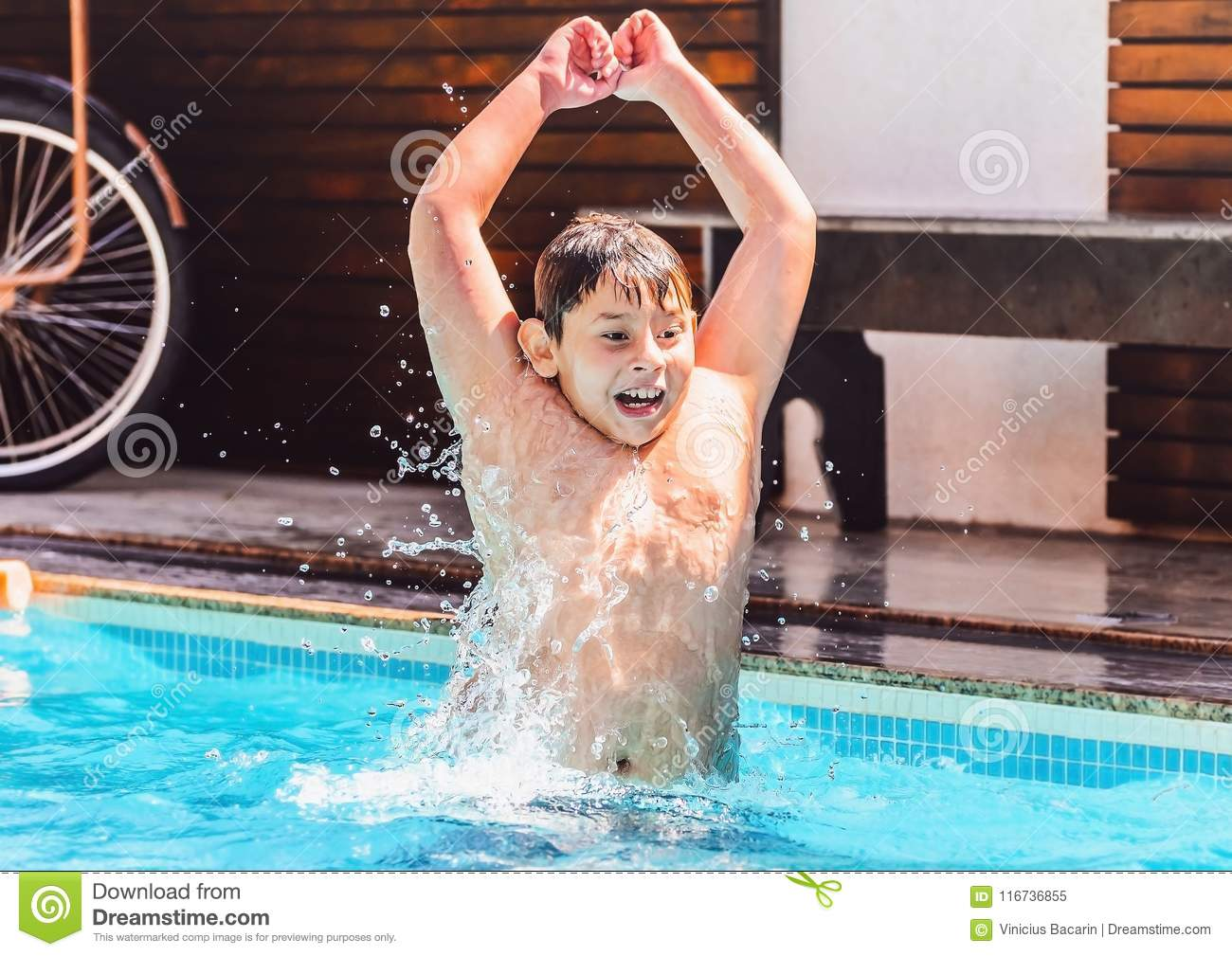 Child`s play, boy going to hit the water, having fun on a summer