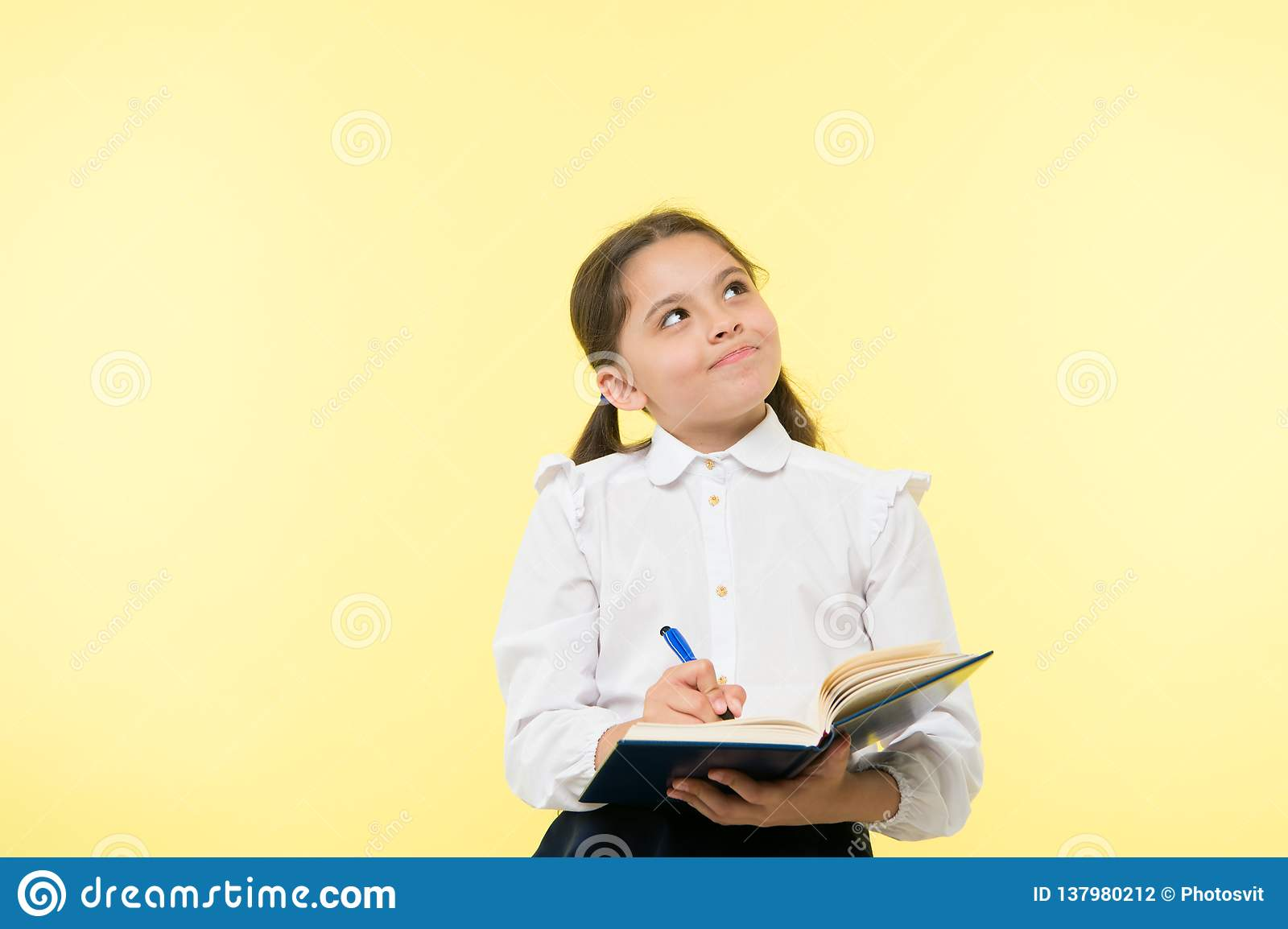 Child school uniform kid doing homework. Child girl school uniform clothes hold book and pen. Girl cute write down idea