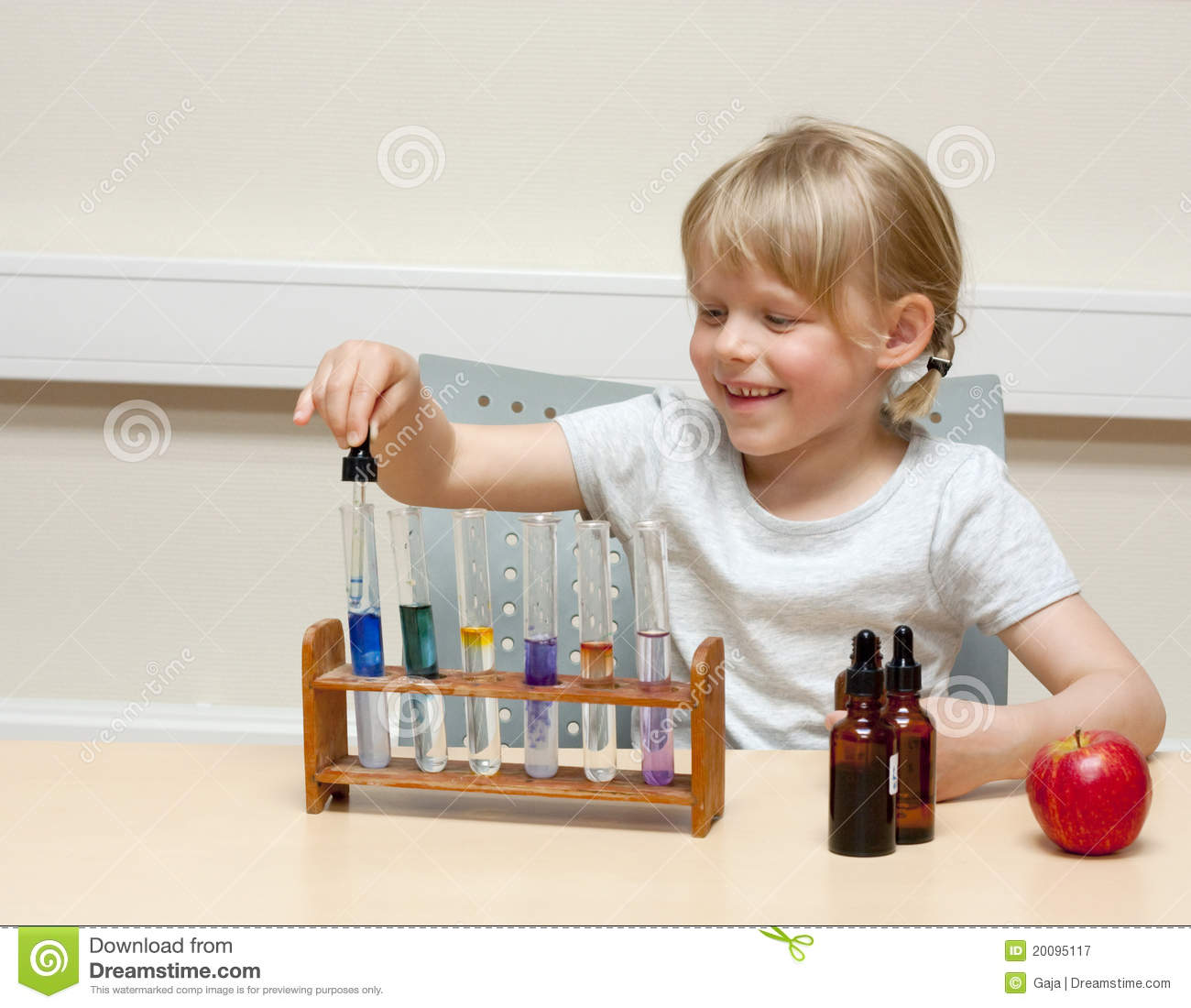 Cute little girl playing with chemistry; using different indicators ...