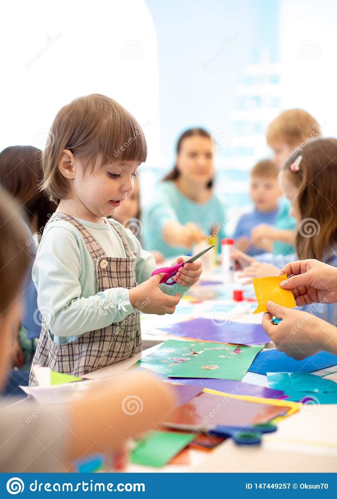 Child with scissors in hands cutting paper with teacher in class room. Group of children doing project in kindergarten