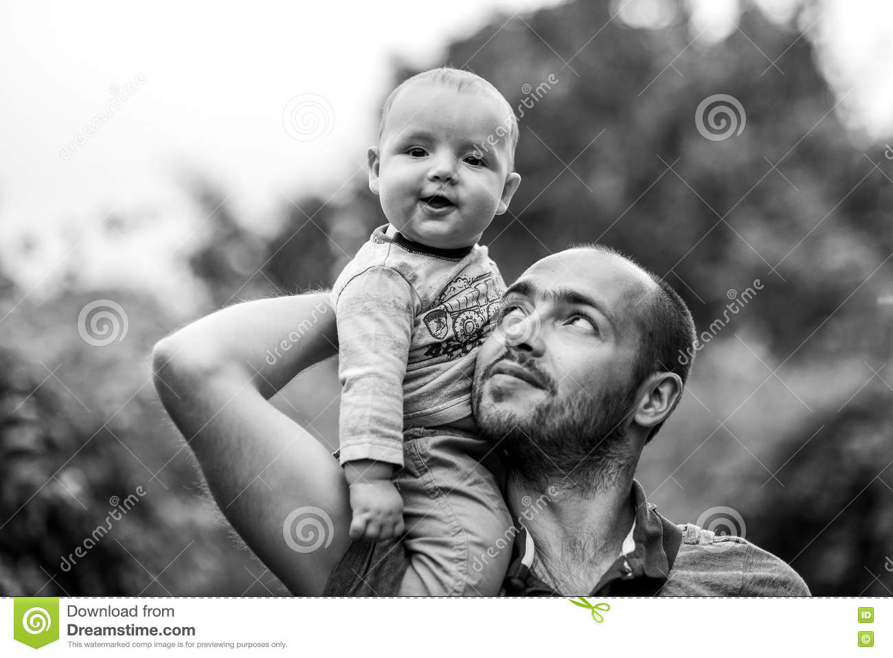 Child sits on dad s shoulder and smiling