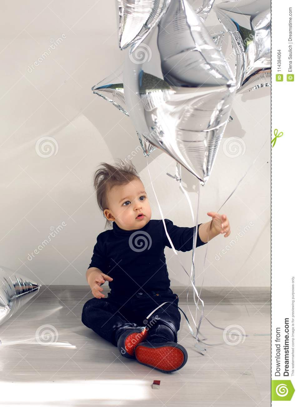 Child sits on the floor with balloons