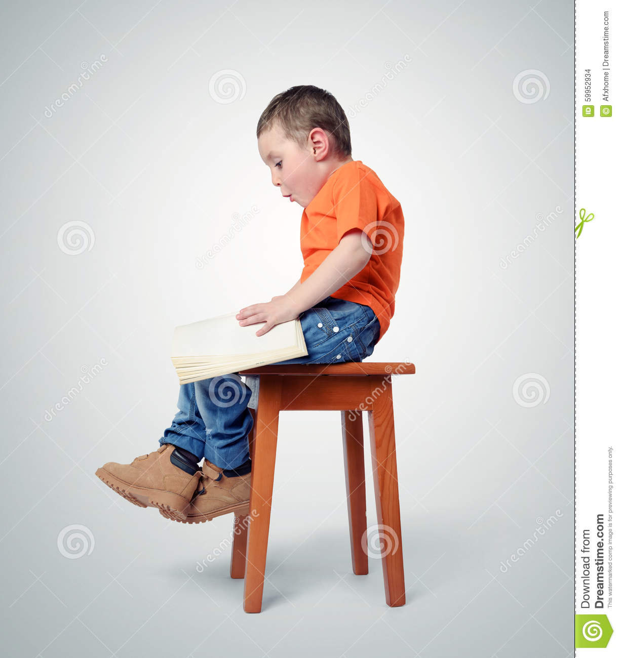 Child Sitting On A Chair With A Book Stock Photo Image