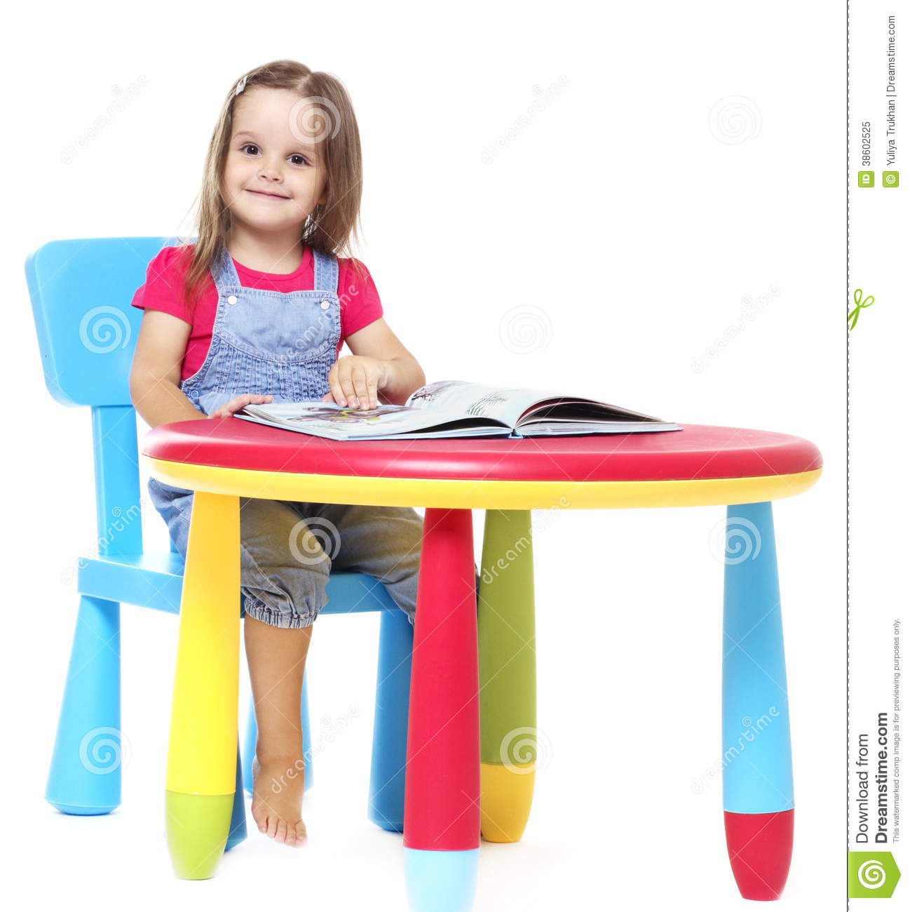 Child Sitting At The Table And Reading A Book Stock Image