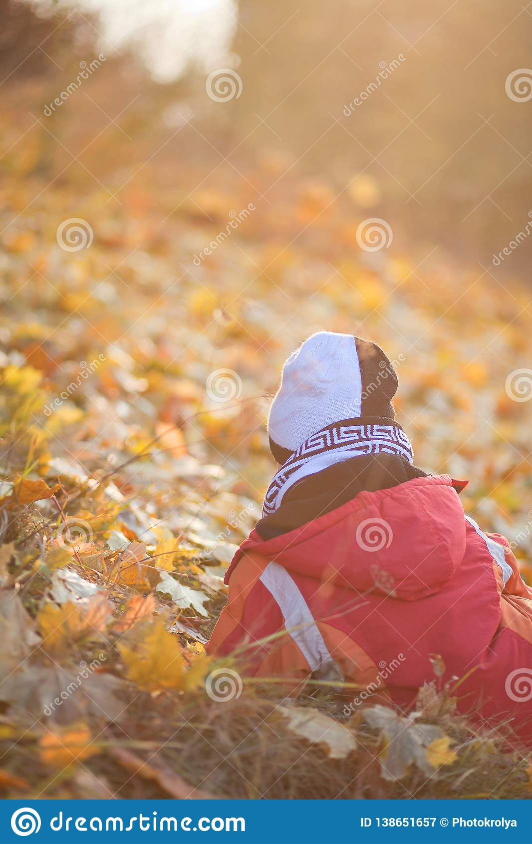 Child sitting and waithing yellow leaves in the autumn park.