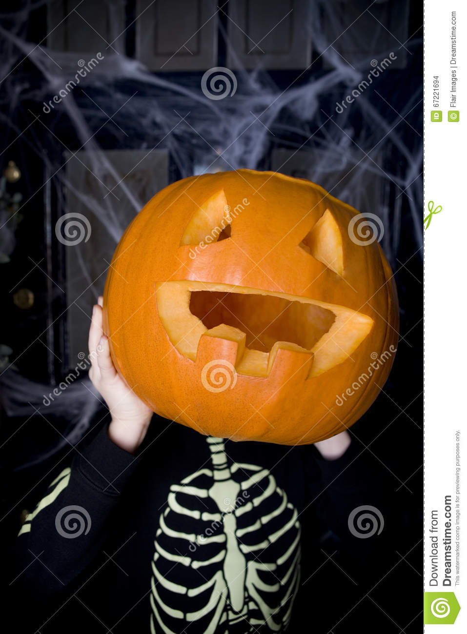 Child in a skeleton costume at a Hallowe en party, holding a pumpkin with a carved face