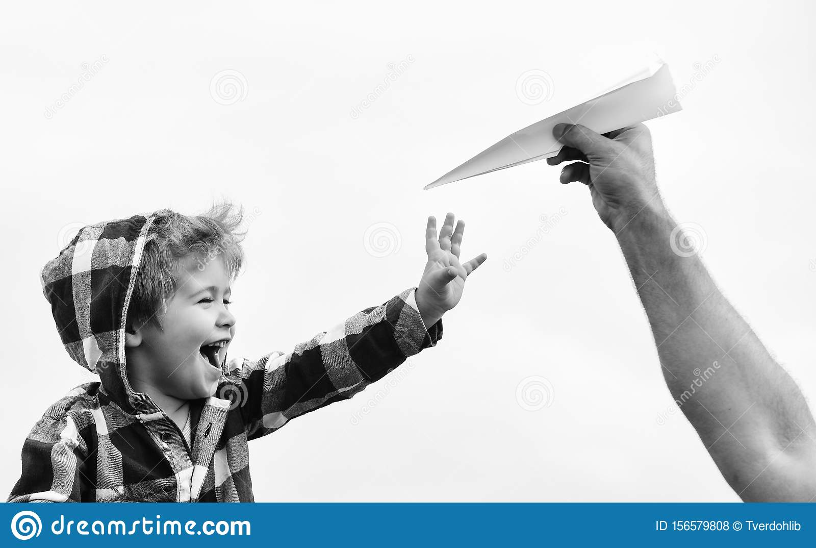 Child son playing with paper airplane. Carefree. Freedom to Dream - Joyful Boy Playing With Paper Airplane. Dream of