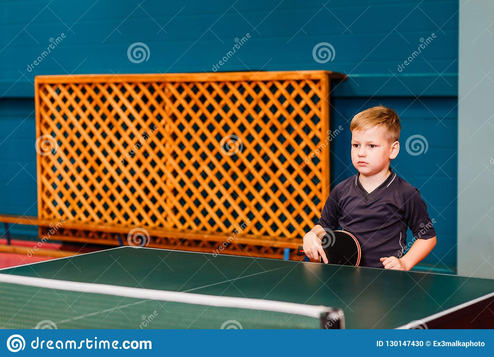 A child stands near the tennis racket with hands