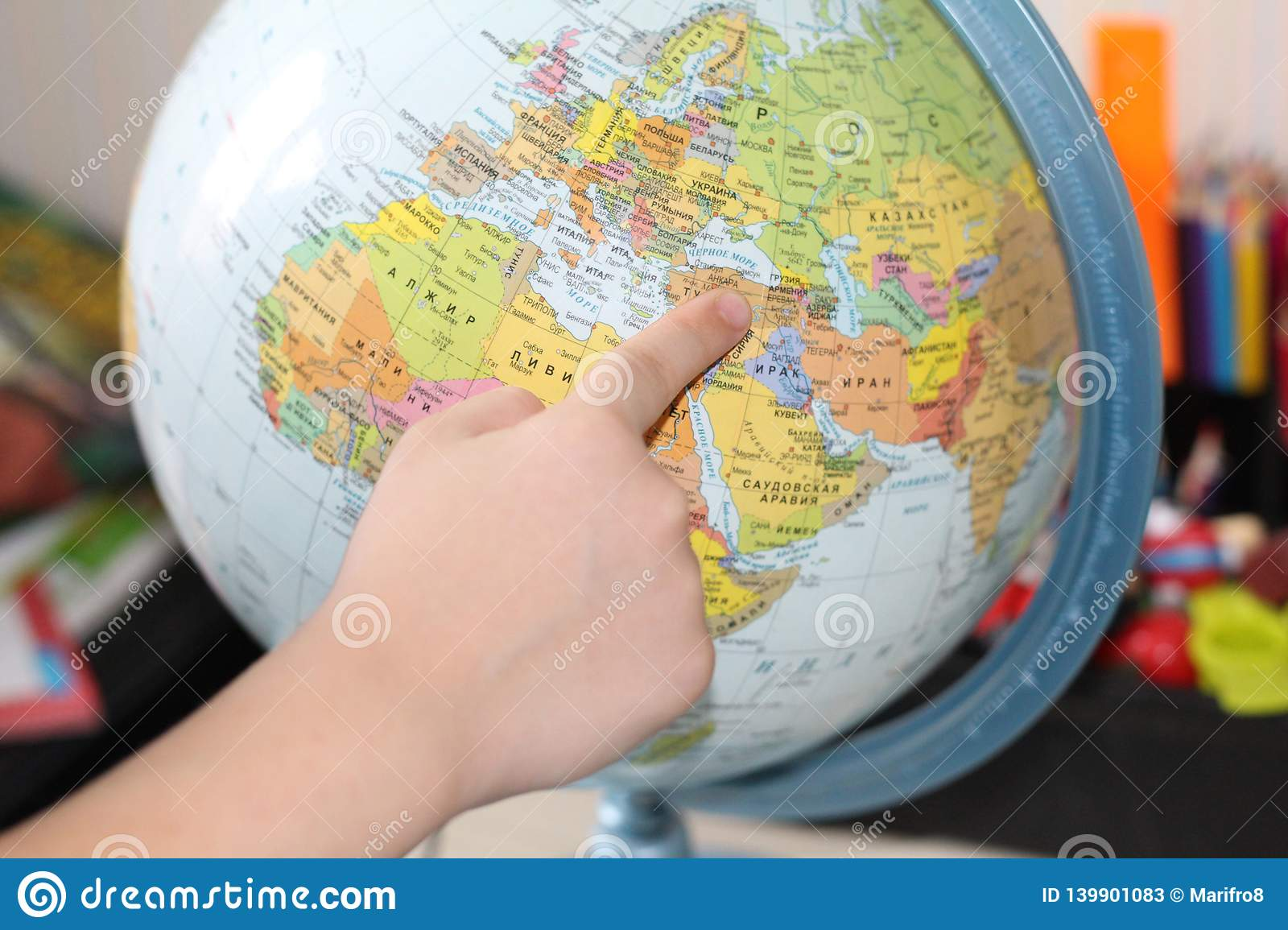 The child is studying geography. Finger pointing to the globe