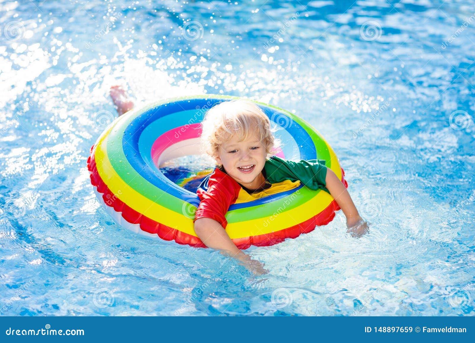 Child in swimming pool on toy ring. Kids swim