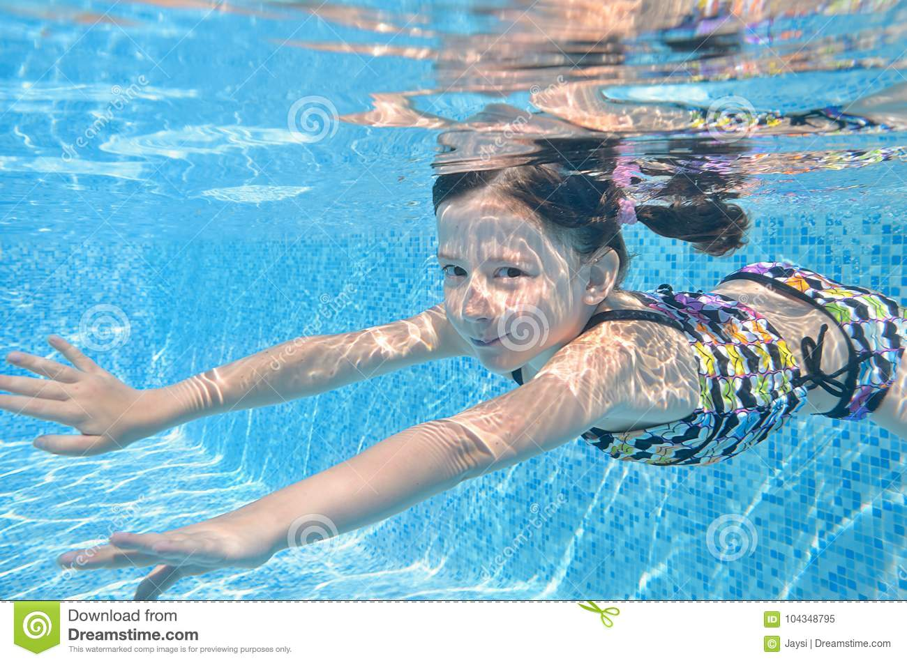 Child swims in pool underwater, happy girl dives and has fun under water, kid fitness and sport on family vacation