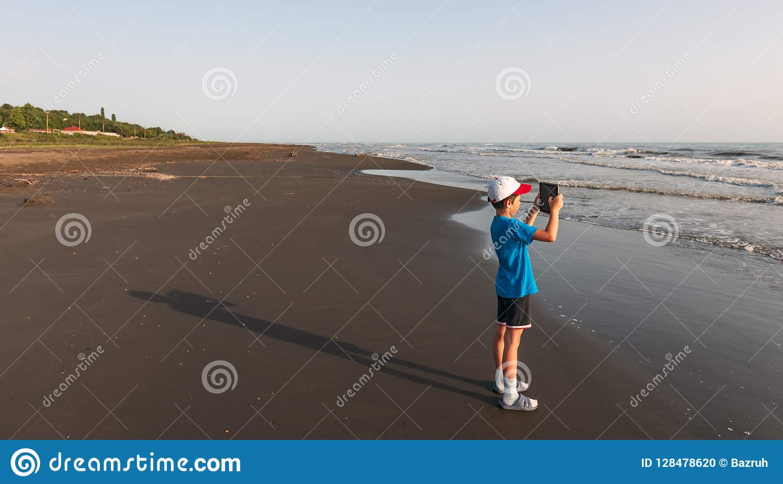 A child with a tablet takes pictures of the sea