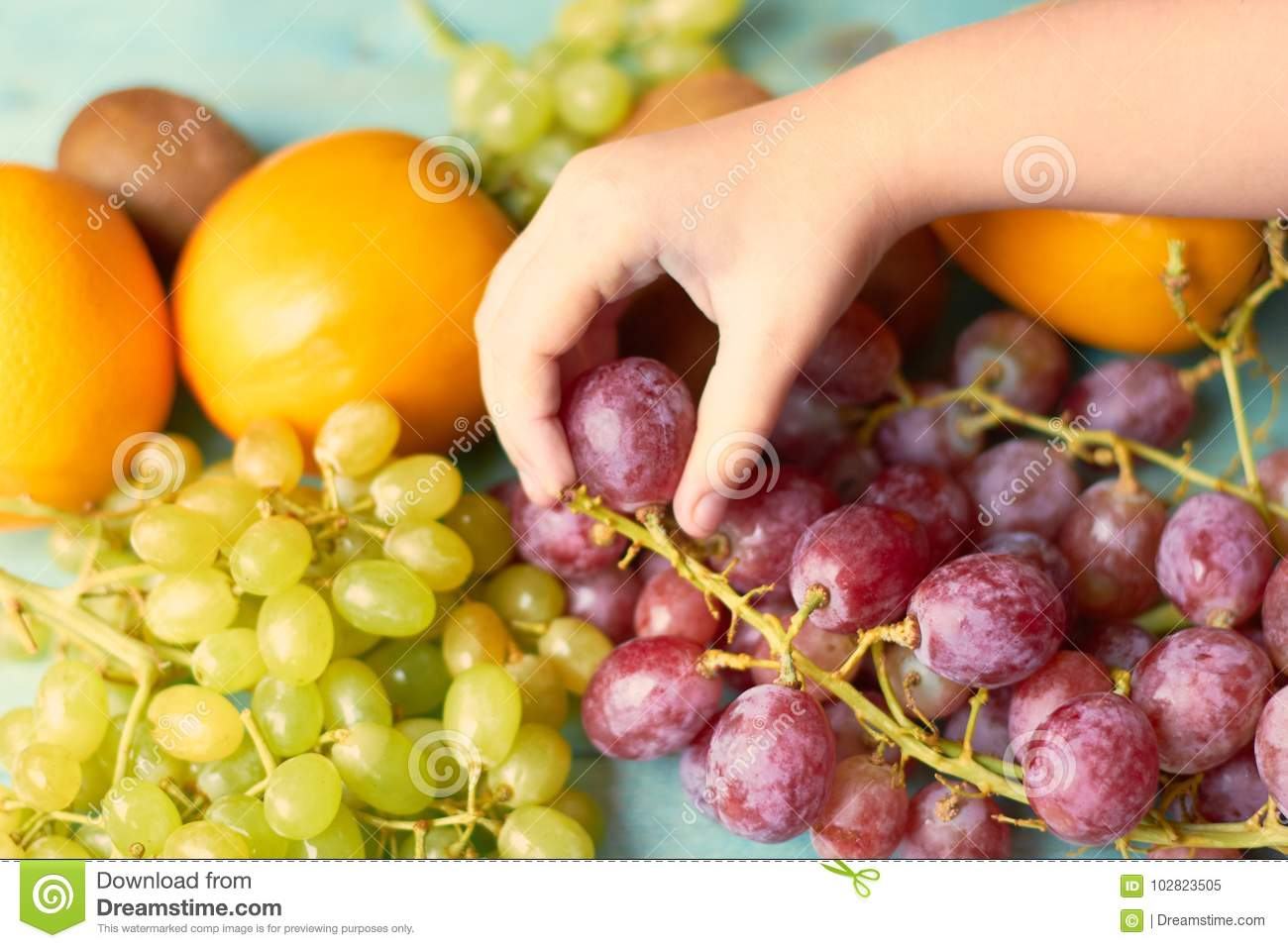 A child takes fruit from a plate