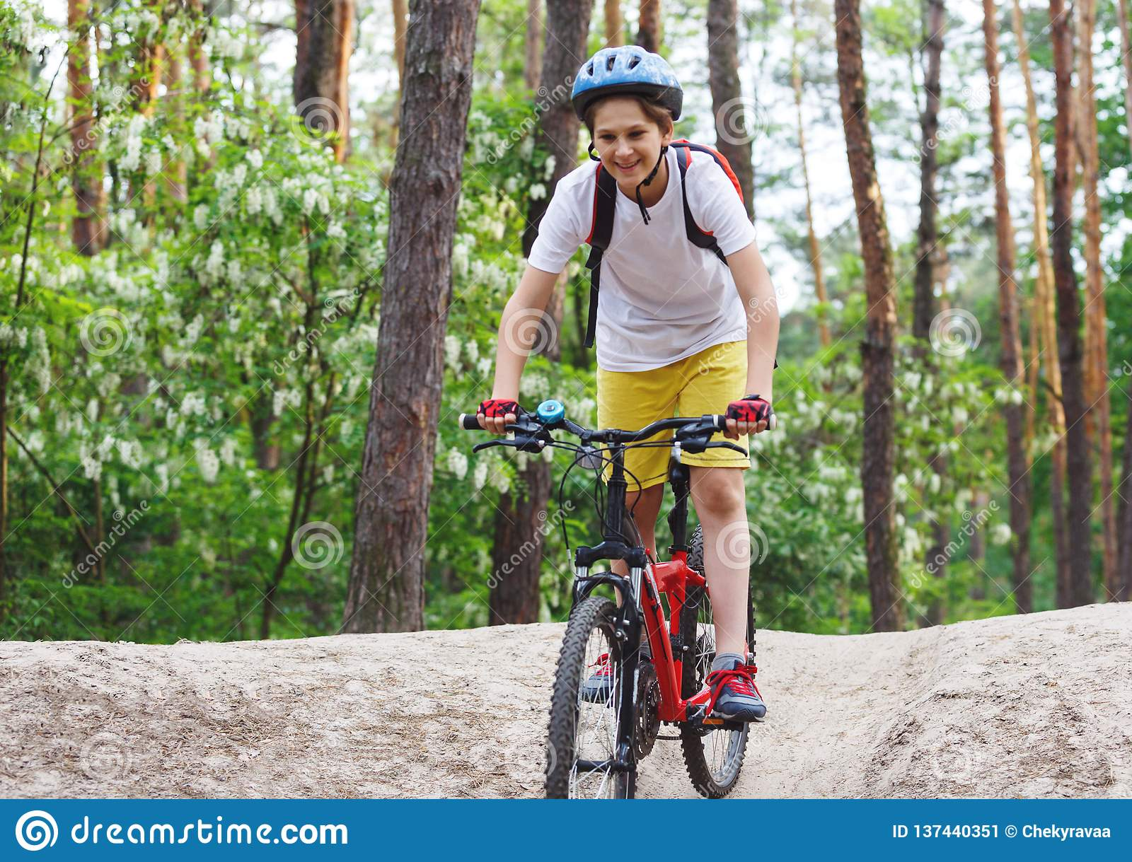 Child teenager in white t shirt and yellow shorts on bicycle ride in forest at spring or summer. Happy smiling Boy cycling