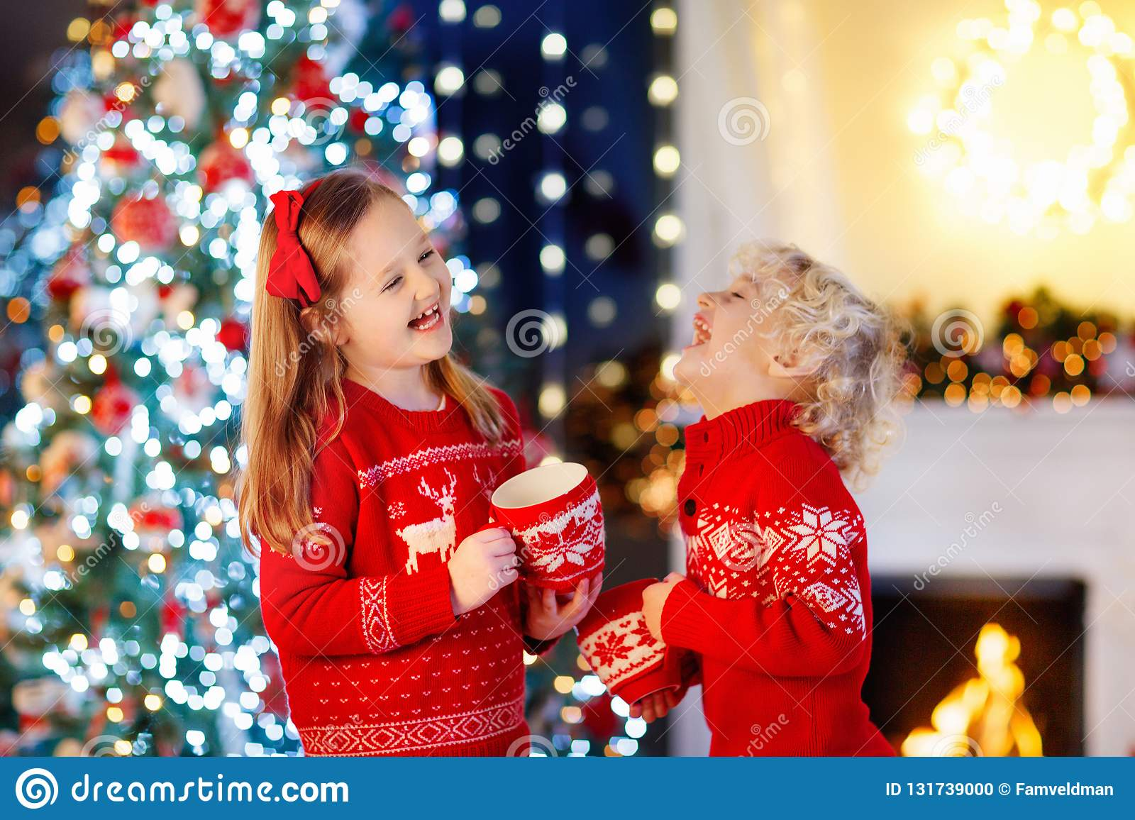 Child under Christmas tree at home. Little boy and girl in knitted sweater with Xmas ornament drink hot chocolate. Family with