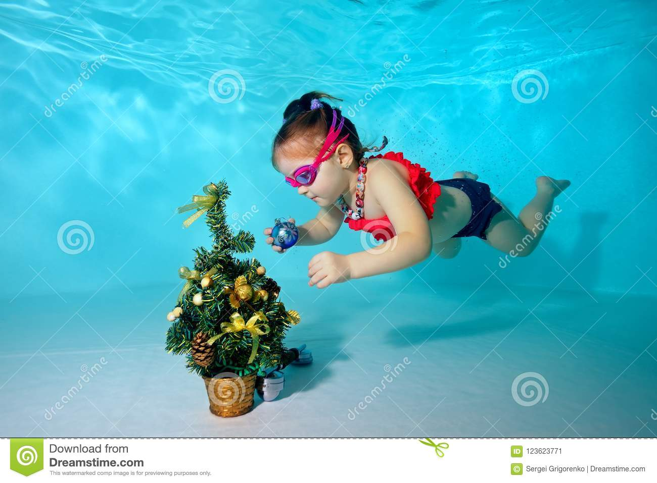 Child Underwater In The Pool Decorates The Christmas Tree With