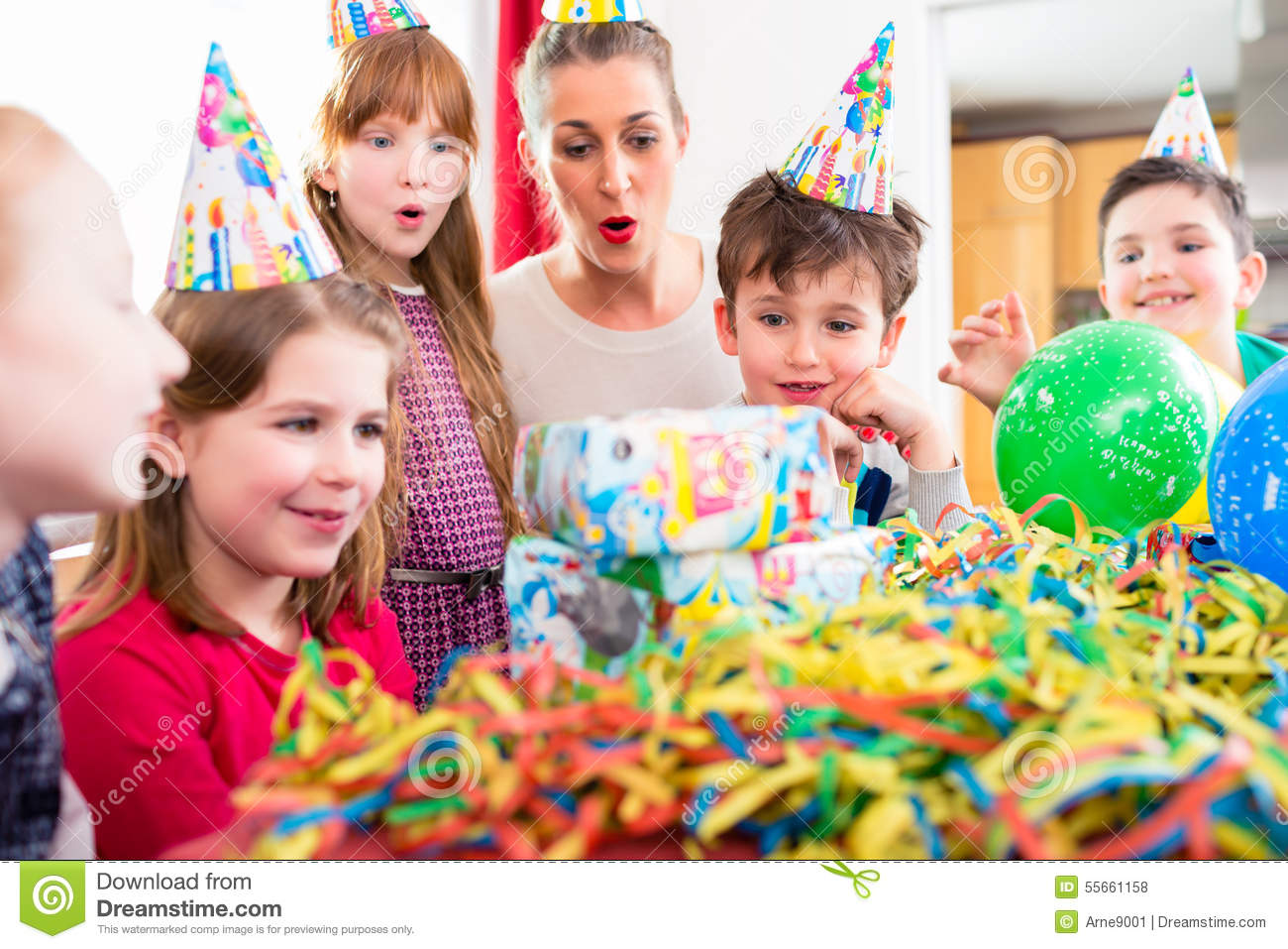 Child Unwrapping Birthday Gift With Friends