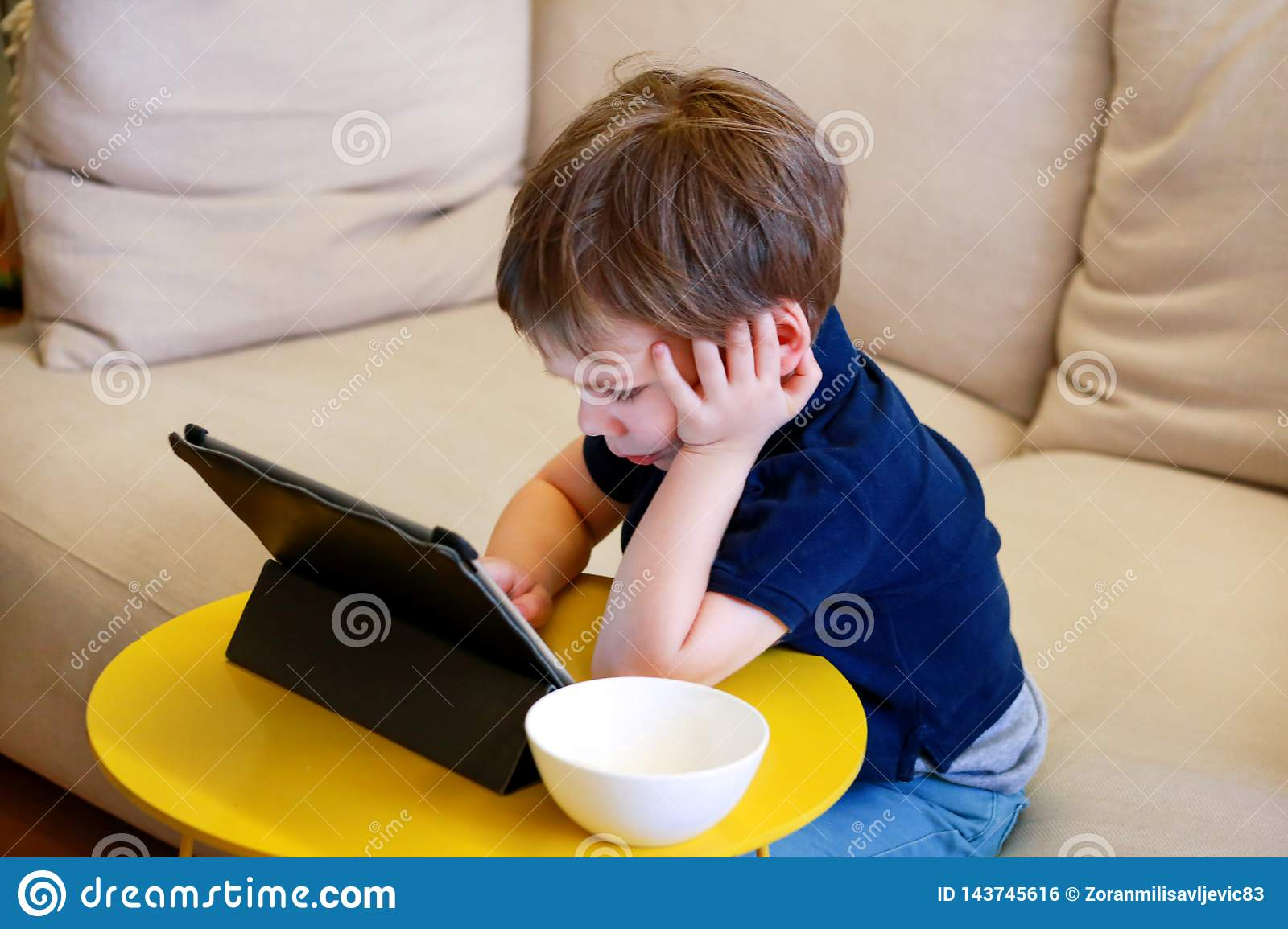 Child using tablet pc on bed at home. Cute boy on sofa is watching cartoon, playing games and learning from laptop. Education, fun