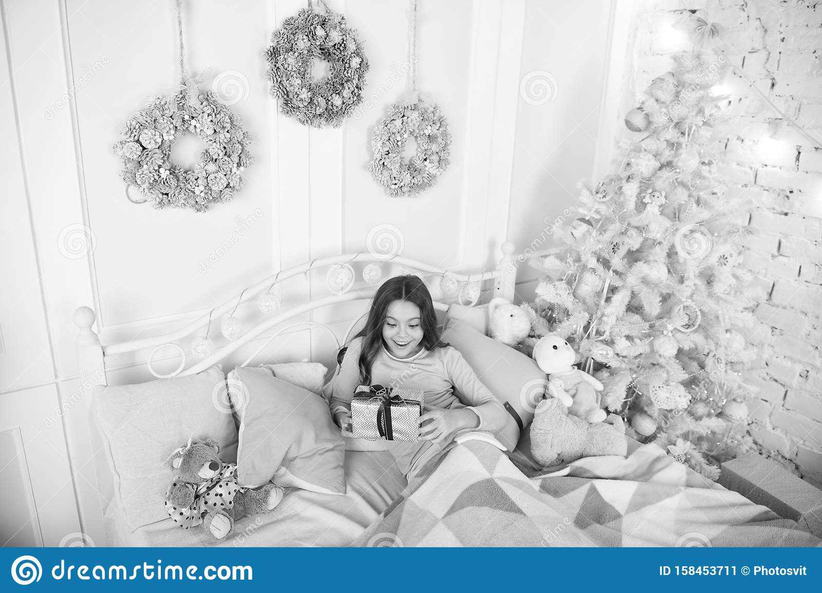 Child waiting christmas in bedroom. Kid lay in bed relaxing. Home is the best place in the world. Girl little kid