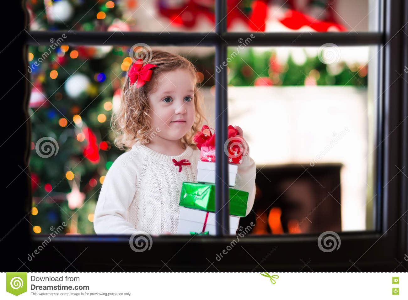 Child Watching Out Of Window On Christmas Eve Stock Photo