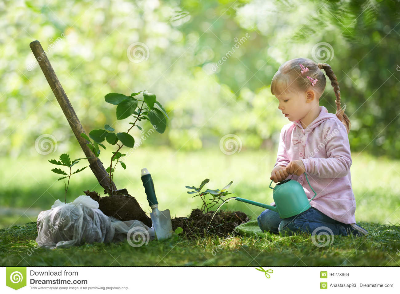 Child watering just planted tree. Children will save the earth