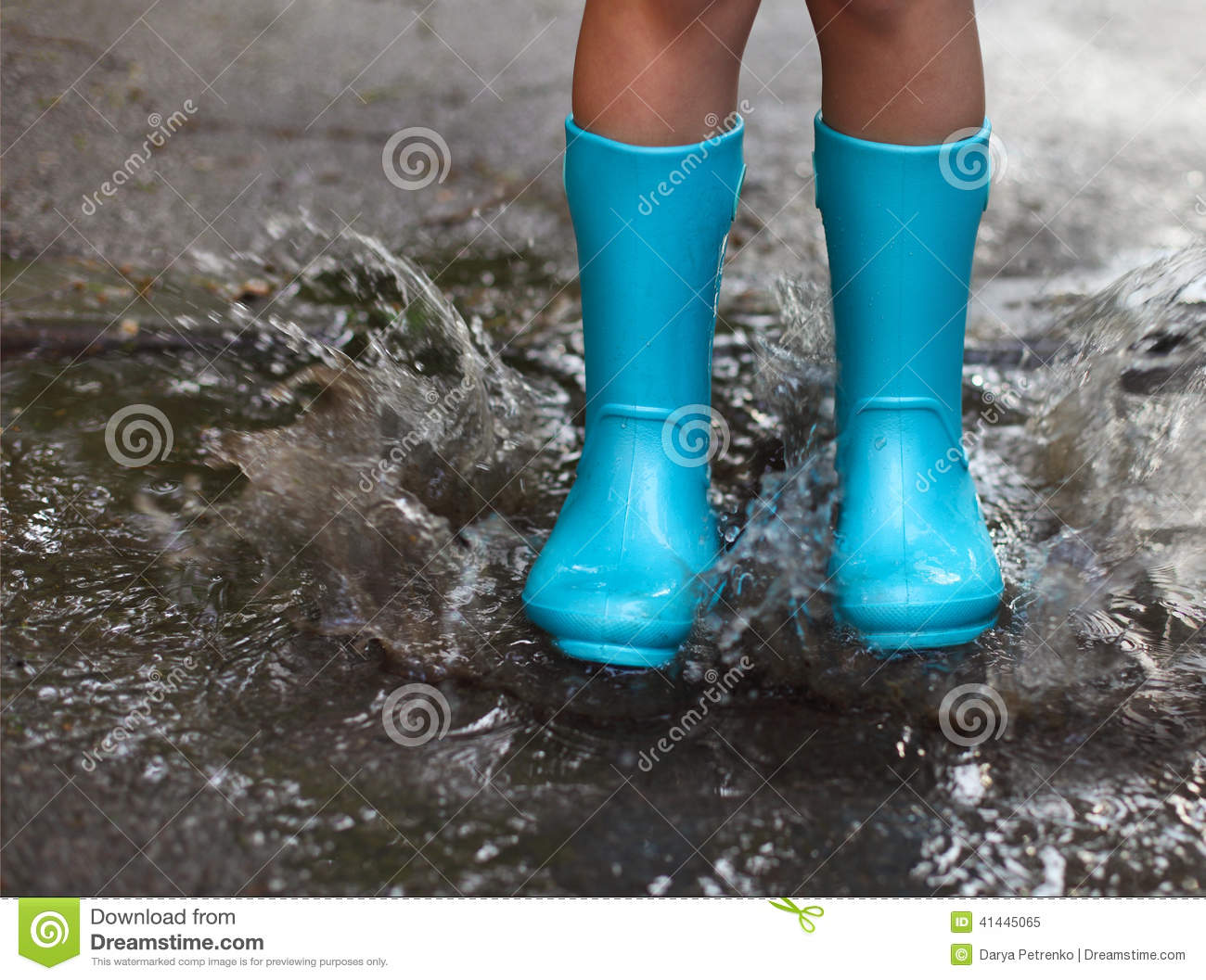 Child Wearing Blue Rain Boots Jumping Into A Puddle Stock
